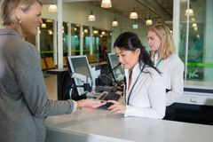 Businesswoman Showing Smart Phone To Receptionist At Airport Cou. Senior businesswoman showing boarding pass on smart phone to receptionist at counter in airport Stock Photos