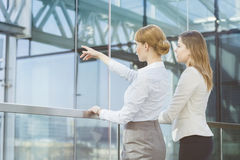 Businesswoman showing something to female colleague from glass wall in office Stock Image