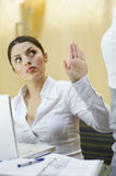 Businesswoman Showing Stop Gesture To Her Colleague Stock Image