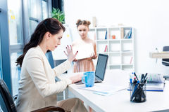 Businesswoman showing stop sign to her daughter with drawing album in office Royalty Free Stock Photo