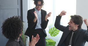 Businesswoman showing success report and celebrating with team at office. Businesswoman showing project achievements report to applauding and cheering colleagues stock video footage