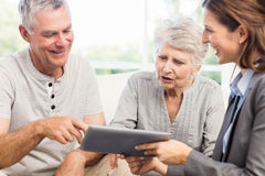 Businesswoman showing tablet to senior couple Royalty Free Stock Photo
