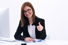 Businesswoman showing thumbs up at her workplace Royalty Free Stock Image