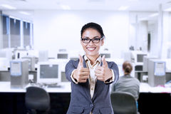 Businesswoman showing thumbs up in the office Royalty Free Stock Photo