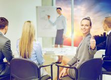 Businesswoman showing thumbs up at office royalty free stock photos