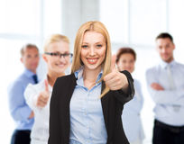 Businesswoman showing thumbs up in office Stock Photo