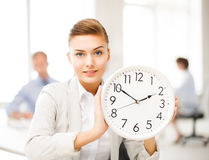 Businesswoman showing white clock in office Stock Image