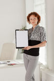 Businesswoman shows blank clipboard. Royalty Free Stock Images