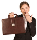 Businesswoman shows briefcase and covers her mouth. Businesswoman shows the briefcase and covers her mouth with joy. Isolated on white background Stock Photos