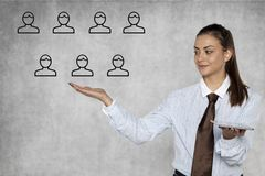 Businesswoman shows how to easily manage people. Isolated on the background Stock Image