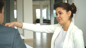 Beautiful businesswoman in a white jacket shows important treaty his colleague in the office stock video