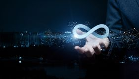 Businesswoman shows sign of infinity on the background of the city. The concept of unlimited Internet stock image