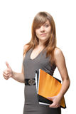 Businesswoman shows thumbs up gesture. A pretty young woman in a grey dress smiles sweetly, holding in one hand the documents, while the other shows a thumbs up royalty free stock photo
