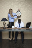 Businesswoman shows at what time the work starts Stock Photography