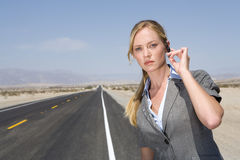 Businesswoman on side of road in desert, hand on earpiece, portrait, close-up Royalty Free Stock Photos