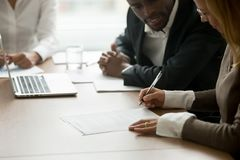 Businesswoman signing business document at diverse partners meet stock photo