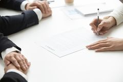 Businesswoman signing business document at group meeting, close. Businesswoman signing business document at group meeting, client customer puts signature on Stock Photography
