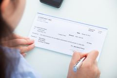 Businesswoman signing on cheque Royalty Free Stock Photos