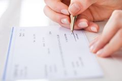 Businesswoman signing cheque Royalty Free Stock Photography
