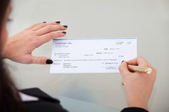 Businesswoman signing cheque Royalty Free Stock Images