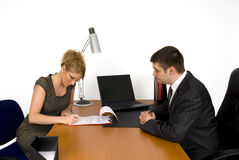 Businesswoman signing the contract. Businesswoman and businessman in office Stock Photos