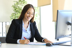 Businesswoman signing a contract. Happy businesswoman signing a contract or document in a desk at office stock photo