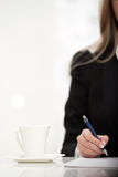 Businesswoman signing on a document with a pen Stock Image