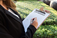Businesswoman signing a life insurance policy on the street.  Royalty Free Stock Photos