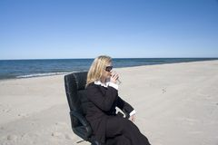 Businesswoman sipping on beach Stock Photos
