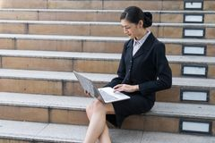 Businesswoman sit on the staircase and typing word into laptop Royalty Free Stock Photo