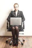 Businesswoman sits on chair with her laptop on wallpaper backgro Royalty Free Stock Photography