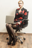 Businesswoman sits on chair  with her laptop Royalty Free Stock Image