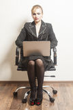 Businesswoman sits on chair with her laptop Royalty Free Stock Images