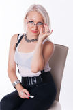 Businesswoman sits on a chair. And looks at you through glasses at the white background stock image