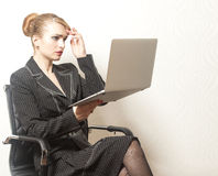 Businesswoman sits on chair and work on laptop Royalty Free Stock Photo