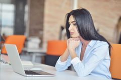Businesswoman sits at a desk in front of a computer Stock Image