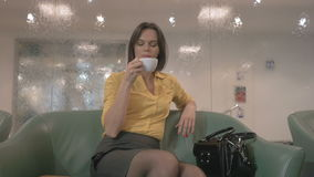 Businesswoman sits in hall of hotel and drink tea. Beautiful businesswoman is sitting in a hall of the hotel. Young woman drinks tea and looks outside the camera stock footage