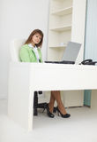 Businesswoman sits at light office with laptop Stock Image