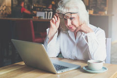 Businesswoman sits at table in front of laptop and looks closely at monitor, raising her glasses. Pensioner freelancer Stock Photo