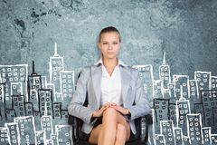 Businesswoman sitting against wall with sketch of Royalty Free Stock Photos