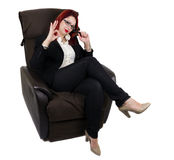 Businesswoman sitting in the armchair with legs crossed. Business woman sitting on the couch, with his legs crossed and pen resting on her cheek. White Royalty Free Stock Photos