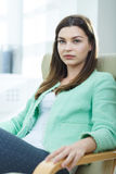 Businesswoman sitting in an armchair Stock Photos