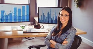 Businesswoman sitting with arms crossed at office Stock Images