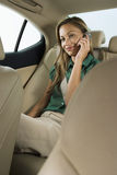 Businesswoman sitting in back seat of car, using mobile phone, smiling Royalty Free Stock Photo
