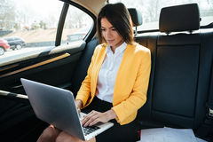 Businesswoman sitting on back seat of car and working Stock Photography