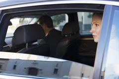 Businesswoman sitting in back-seat of chauffeur driven car, looking out of open window, side view Stock Image