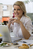Businesswoman sitting at balcony table with laptop, holding mug of coffee, smiling, portrait Stock Photo