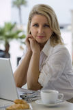 Businesswoman sitting at balcony table with laptop, smiling, side view, portrait Stock Photos