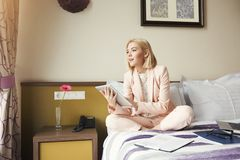 Businesswoman sitting on bed and using tablet. Beautiful businesswoman sitting on bed and using tablet. Woman working in hotel room. Business lady went to Royalty Free Stock Photography