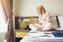 Businesswoman sitting on bed and using tablet. Beautiful businesswoman sitting on bed and using tablet. Woman working in hotel room. Business lady went to Stock Photography